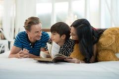 Le papa et la maman regardant mon fils lisant un livre est sur le lit en Th Photos stock