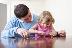 Le papa et le descendant met des pièces de monnaie Photo libre de droits