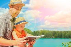 Le papa heureux avec l'enfant a lu le livre de bible photo libre de droits