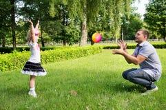 Le papa joue avec sa fille avec la boule photos stock