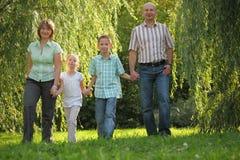 Le papa, la maman et les enfants marche en stationnement d'automne Photos libres de droits