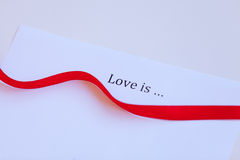 Le papier avec amour de mots est et ruban Photos libres de droits