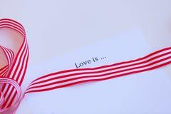 Le papier avec amour de mots est et ruban Image libre de droits