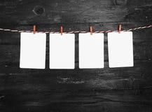 Le papier blanc ou la photo encadre accrocher sur la corde à linge rayée rouge Fond en bois Descripteur pour votre texte Photos libres de droits