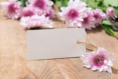 Le papier blanc vide d'étiquette avec la couleur fleurit sur le fond en bois T Images libres de droits