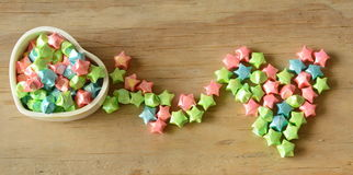 Le papier coloré d'étoile de la boîte transforment à la forme de coeur sur le fond en bois Photographie stock