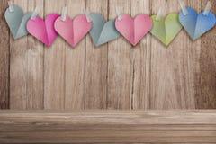 Le papier coloré de forme de coeur a coupé le bâton de style sur le vieux backgro en bois Photos stock
