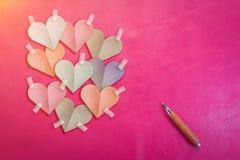 Le papier coloré de forme de coeur a coupé le bâton sur le fond rose de couleur Photo stock