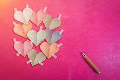 Le papier coloré de forme de coeur a coupé le bâton sur le fond rose de couleur Photos stock