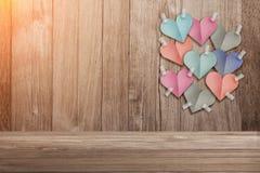Le papier coloré de forme de coeur a coupé le bâton sur le vieux fond en bois Photographie stock libre de droits