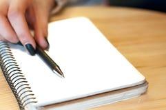 le papier dans les notes femelles d'écriture de main de femme d'affaires sur une table noircissent la manucure et la lettre vide Image libre de droits