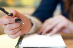 le papier dans les notes femelles d'écriture de main de femme d'affaires sur une table noircissent la manucure et la lettre vide Photographie stock libre de droits