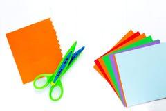 Le papier de couleur pour l'origami est une fan, ciseaux avec un bord onduleux Sur la table blanche photo libre de droits