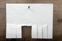 Le papier de publicité avec la coupure glisse sur le fond en bois photos stock