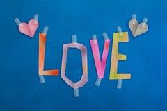 Le papier des textes de mot d'amour a coupé avec le coeur sur le fond en cuir bleu Photos stock
