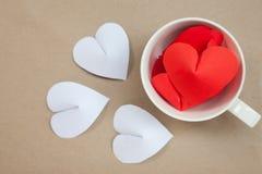 Le papier en forme de coeur dans la tasse de café arrangent comme fond Image stock