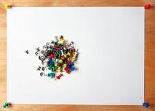Le papier et beaucoup colorent des punaises rouges, bleu, vert, jaune, blanc Une feuille de fixé au conseil en bois Image stock
