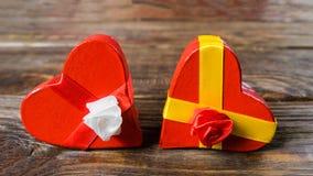 Le papier-pierre de boîte-cadeau sous forme de coeurs rouges attachés avec des rubans et des cadeaux de satin a emballé par le pa Photos libres de droits
