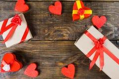 Le papier-pierre de boîte-cadeau sous forme de coeurs rouges attachés avec des rubans et des cadeaux de satin a emballé par le pa Images stock