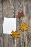 Le papier pour les feuilles de lettre et de couleur d'un érable sont sur une surface en bois image stock