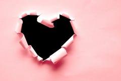 Le papier rose a déchiré dans la forme de coeur avec l'espace noir Image stock