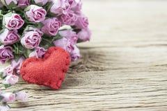 Le papier rose s'est levé avec le coeur rouge sur le vieux bois Photographie stock libre de droits