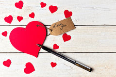 Le papier rouge de coeur a coupé sur le fond en bois blanc Image libre de droits
