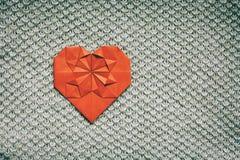 Le papier rouge a plié le coeur fait main d'origami sur le fond gentil tricoté peu commun intéressant brun naturel de couverture  photographie stock