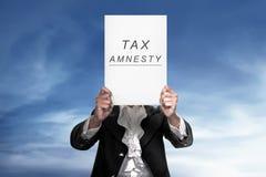 Le papier se tenant humain lit l'amnistie d'impôt Image libre de droits