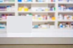Le paquet blanc vide de médecine sur le compteur avec la tache floue rayonne image stock