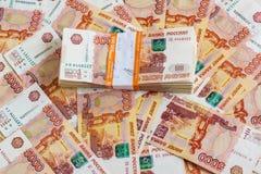 Le paquet des cinq millième notes de rouble dans un demi-million de roubles russes se trouve sur le fond des billets de banque di Images stock