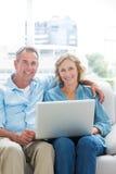 Le par som kopplar av på deras soffa genom att använda bärbara datorn arkivfoton