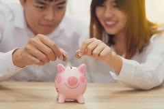 Le par som sätter ett mynt in i en rosa spargris för att köpa ho arkivbild