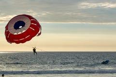 Le parachute a poussé en hors-bord en mer avec des vacances de coucher du soleil photo stock