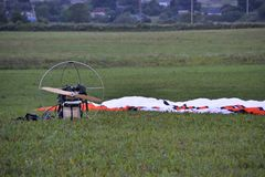 Le parapentiste après les supports de vol sur l'herbe verte dans le domaine, le dôme et l'aile sont abaissés à la terre image stock