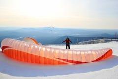 Le parapentiste presque se prépare au décollage aux montagnes Horizontal de l'hiver photographie stock