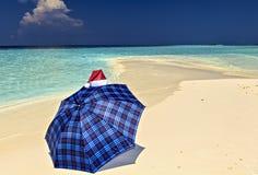 Le parapluie bleu est sur une plage avec Santa Hat Images libres de droits