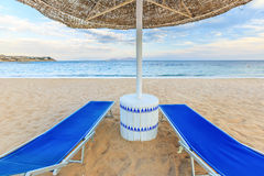 Le parapluie et deux chaises longues vides sur le sable de rivage échouent Photo stock