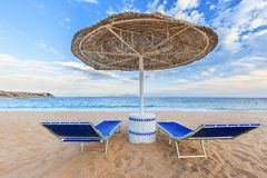Le parapluie et deux chaises longues vides sur le sable de rivage échouent Photos stock