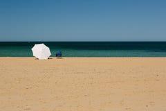 Le parapluie et la chaise longue sur Mordialloc échouent, Melbourne photos stock