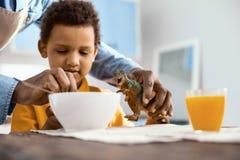 Le parent de soin aidant son petit fils alimentent le dinosaure de jouet Image libre de droits