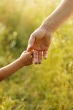 Le parent tient la main d'un petit enfant Photo libre de droits