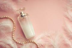 Le parfum des femmes sur un fond rose sensible avec des plumes photos libres de droits