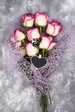 Le parfum du ` s de femmes dans la belle bouteille verte de coeur et la rose de rose fleurissent Photographie stock