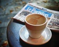 Le Parisien newspaper. Paris, France - September 9, 2017: An empty coffee cup and Le Parisien newspaper on the cafe table Royalty Free Stock Photo