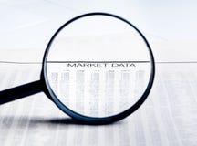 Le parole di dati del mercato vedono attraverso la lente della lente di ingrandimento sul giornale finanziario Fotografie Stock Libere da Diritti