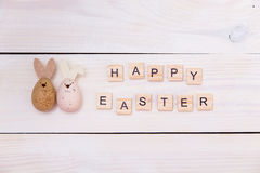 Le parole di Pasqua felice sono scritte sui cubi e sulle uova di legno Concetto felice di Pasqua su fondo di legno bianco Fotografie Stock Libere da Diritti