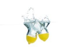Le parti del limone sono caduto in acqua con spruzzata Immagine Stock
