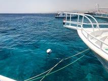 Le parti nasali delle navi bianche hanno attraccato, stando nel mare blu aperto sul bacino contro il mare blu Fotografie Stock