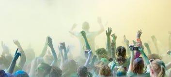 Le participant dans la couleur courent écarter les bras dans le ciel Image libre de droits